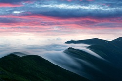 Amazing flowing morning fog in spring mountains blurred from long exposure. Beautiful sunrise on background. Landscape photography