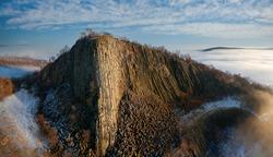 Amazing geological formatoion with fog. Basalt columns hill in upper Balaton region in Hungary. The hungarian name is Hegyesstu.