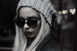 Amazing girl Autumn,spring fashion Outfit. Style hipster trend Girl Swag beanie hat. Stylish vintage glasses.Monochrome outdoor portrait of young fashionable woman with long hair posing in street.
