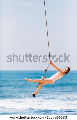 Amazing girl swings near the ocean  #1037685583