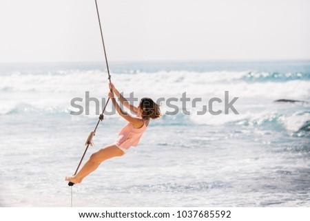 Amazing girl swings near the ocean  #1037685592