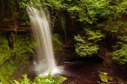 Amazing Glencar Waterfall surrounded by green foliage. County Lietrim, Ireland. Popular tourist attraction