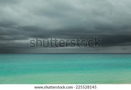 Amazing, gorgeous view of horizon line and upcoming rain storm with dark, dramatic grey cloudy sky above tranquil azure  Atlantic ocean at Cuban Santa Maria island