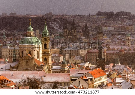 Amazing Gothic church of Our Lady and St. Nicolas church during winter day with heavy snow storm and sun rays peeping through clouds, Prague, Czech republic #473211877