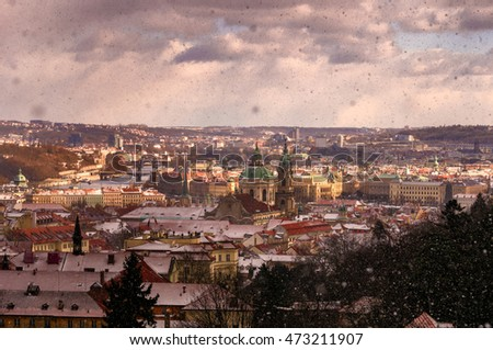 Amazing Gothic church of Our Lady and St. Nicolas church during winter day with heavy snow storm and sun rays peeping through clouds, Prague, Czech republic #473211907