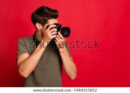 Amazing guy with photo digicam making pictures wear casual grey t-shirt isolated on red background