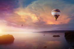 Amazing heavenly background - two colorful hot air balloons flies in glowing sunset sky above calm sea