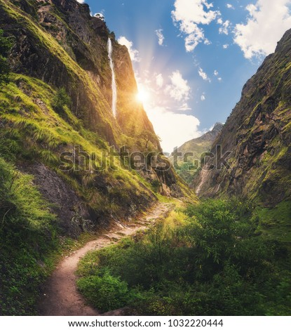 Amazing Himalayan mountains covered green grass, high waterfall, beautiful path, green trees, blue sky with yellow sun and clouds in Nepal at sunset. Mountain canyon. Travel in Himalayas.Landscape #1032220444