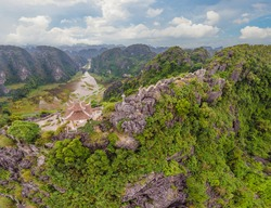 Amazing huge dragon statue at limestone mountain top near Hang Mua view point at foggy morning. Popular tourist attraction at Tam Coc, Ninh Binh. Vietnam travel landscapes and destinations. Vietnam