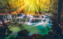 Amazing  in colorful autumn forest with light of God for hope in life everlasting life,Special light yellow orange blue-green water ,abstract religious beliefs. erawan waterfall kanchanaburi asia .