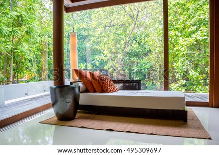 Amazing interior design. Panoramic view of nice cozy bedroom with tropical jungle view outside. Beautiful Maldives
