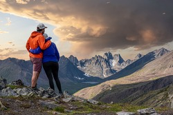 Amazing jagged mountain view in northern Canada, Yukon Tombstone Territorial Park with couple hugging. Orange and purple clothing with stormy looking sky in background.