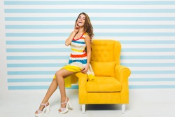 Amazing joyful girl with long tanned legs sitting on yellow armchair and touching her face with hand. Portrait of stunning young lady wearing trendy sandals and colorful attire.