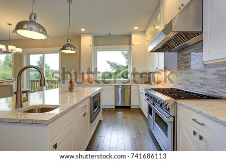 Amazing kitchen design with white shaker cabinets paired with gray marble counters, large kitchen peninsula and high-end stainless steel appliances.