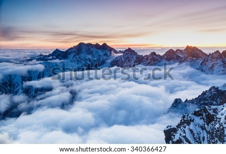 Stock Photo Amazing landscape and rugged mountains raise above the clouds and fog shortly before sunrise
