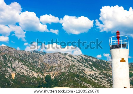 Stock Photo Amazing landscape. View of the lighthouse, in the background mountains, sky, snow-white clouds. The island of the Virgin on the reef in the Bay of Kotor, Montenegro, August 2018