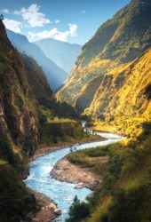 Amazing landscape with high Himalayan mountains, beautiful curving river, green forest, blue sky with clouds and yellow sunlight in autumn in Nepal. Mountain valley. Travel in Himalayas. Nature