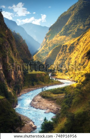 Amazing landscape with high Himalayan mountains, beautiful curving river, green forest, blue sky with clouds and yellow sunlight in autumn in Nepal. Mountain valley. Travel in Himalayas. Nature #748916956