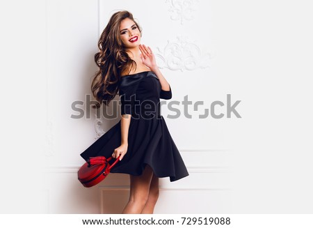 Amazing luxury seductive  woman in stylish  black  party dress posing on white  wall . Red hand bag . Bright smokey eyes make up, healthy wavy hairs. Fashion portrait. Celebrating   birthday  party.