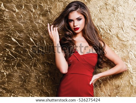 Amazing luxury woman in stylish red party dress posing on gold shining  wall . Bright  smokey eyes make up, red full lips,  healthy wavy hairs.