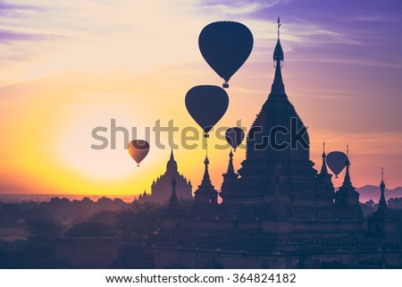 Amazing misty sunrise colors and balloons silhouettes over ancient Dhammayan Gyi Pagoda. Architecture of old Buddhist Temples at Bagan Kingdom. Myanmar (Burma). Travel landscapes and destinations #364824182