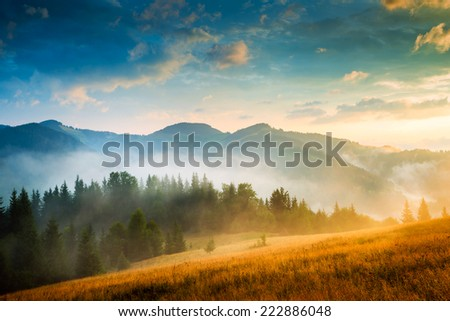 Stock Photo Amazing mountain landscape with fog and a haystack
