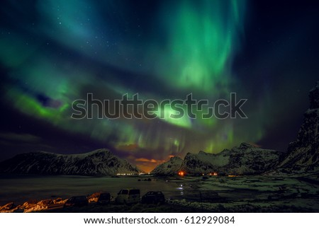 Stock Photo Amazing multicolored green Aurora Borealis also know as Northern Lights in the night sky over Lofoten landscape, Norway, Scandinavia.