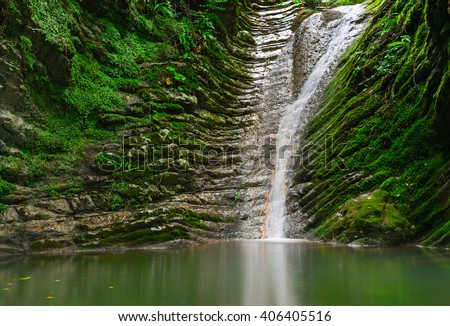 Amazing natural view of  small waterfall in deep forest landscape.Scenery of russian nature with awesome water - stock photo