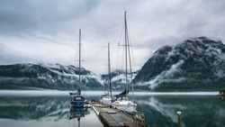 Amazing nature landscape view of lake surrounded by foggy mountains. Sailing vessels or ships. Nature lake. Forest natural. Location: Scandinavian Mountains, Norway. Artistic picture. Beauty world.