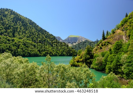 Amazing nature landscape view of lake with incredible color of water surrounded by peaks of mountain forest and blue sky as a background. Natural scenery of high ground and green trees growing on it. #463248518