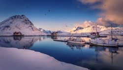 Amazing nature scenery. Winter landscape during sunrise. winter mountains and fjord with typical rorbu and fishing boats on calm water. Lofoten islands. North Norway. Scenic image scandinavian nature.