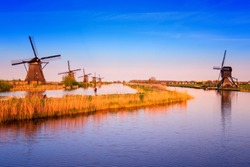 Amazing nature, scenic sunset landscape, windmills, blue sky and water. Traditional dutch countryside, famous village of mills Kinderdijk, popular tourist attraction in Netherlands (Holland)