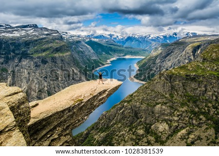 Amazing nature view with Trolltunga and a girl standing  on it. Location: Scandinavian Mountains, Norway, Stavanger. Artistic picture. Beauty world. The feeling of complete freedom