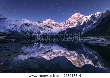 Amazing night scene with himalayan mountains and mountain lake at starry night in Nepal. Landscape with high rocks with snowy peak and sky with stars reflected in water. Beautiful Manaslu, Himalayas