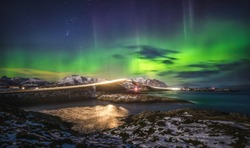 Amazing night sky with Aurora Borealis over Atlantic Ocean Road in Norway. View on the famous bridge and lights from running car.