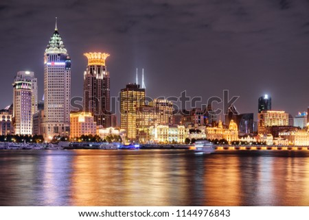 Amazing night view of Puxi skyline in Shanghai, China. Modern and old buildings of the Bund (Waitan) at historic center. Colorful city lights reflected in water of the Huangpu River. #1144976843