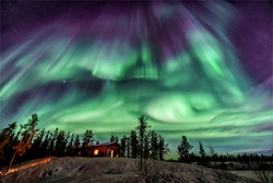 Amazing Northen Lights in purple and blue color dancing over chalet in Yellowknife