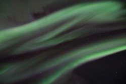 Amazing northern lights movement in the dark night sky in Norway. beautiful and unique colors green and purple.