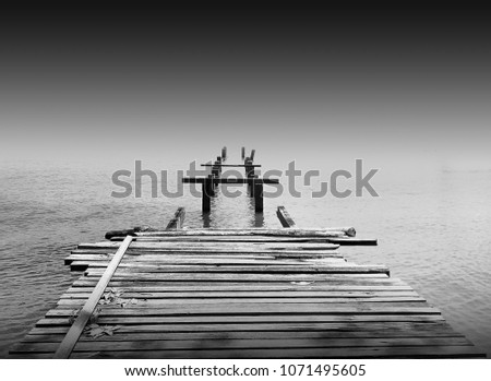 Amazing old abandon wooden jetty in minimalist black and white fine art photography. (blurry soft focus noise grain visible full resolution) Nature composition
