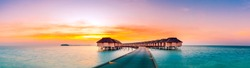 Amazing panorama beach landscape. Maldives sunset seascape view. Horizon with sea and colorful sky. Luxury resort for vacation and holiday concept. Tropical sunset beach