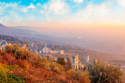 Amazing panorama view of Assisi, province of Umbria city skyline and skyscraper at sunset. Beautiful night view from hill, seen St. Francis church or Basilica and hill in background