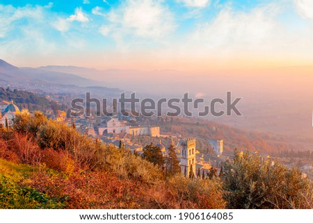 Amazing panorama view of Assisi, province of Umbria city skyline and skyscraper at sunset. Beautiful night view from hill, seen St. Francis church or Basilica and hill in background Stock photo ©