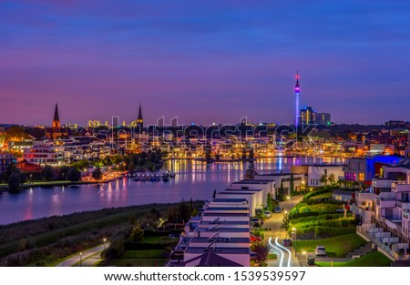 Photo of  Amazing panoramic view of Phoenix Lake in Dortmund, Germany over city skyline and Florian Tower illuminated at twilight. It is an artificial lake and recreational area on the former steelworks