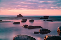 Amazing perfect pink dreamy looking sunset. Slow shutter speed photos of sunset. Smooth water and colorful clody sky. Sunset through straws. Stones on the beach. Wallpaper. Little blur - dreamy look