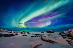 Amazing phenomenon - Aurora Borealis   over Uttakleiv Beach on Lofoten islands in Norway, Scandinavia, Europe. Northern lights - green ray of light in high stratosphere levels. Night winter landscape.