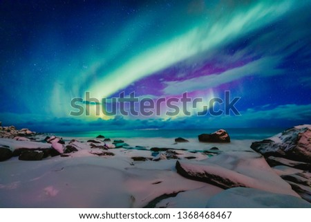Amazing phenomenon - Aurora Borealis   over Uttakleiv Beach on Lofoten islands in Norway, Scandinavia, Europe. Northern lights - green ray of light in high stratosphere levels. Night winter landscape. #1368468467