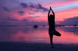 Amazing pink and violet sky with silhouette of a girl, greeting the sun yoga