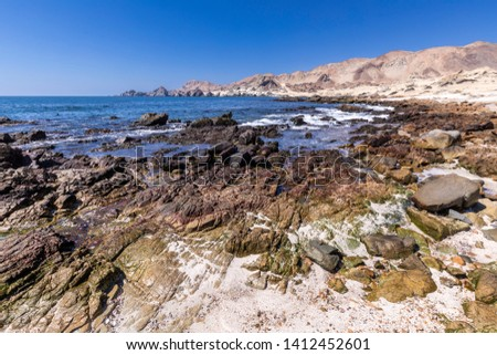 Amazing pools in a wild rocky beach at Atacama Desert. Awe wilderness landscape with the Pacific Ocean waters crashing Chilean coastline on an idyllic environment inside the driest desert in the world #1412452601