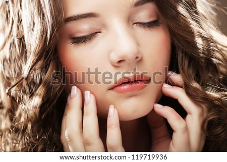 Amazing portrait of beautiful young woman with curly hair. Close-up face studio photo.