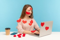 Amazing positive woman with kind expression sitting all covered with sticker love hearts and typing on laptop, dating chatting online, romantic relationship on internet. indoor studio shot, isolated